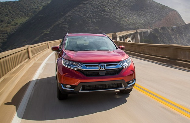 Red 2019 Honda CR-V drives along a highway in the mountains.