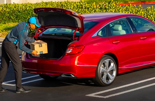 A man in a blue cap loads a package from Amazon into the back of a 2020 Honda Accord, now available at Pohanka Honda.