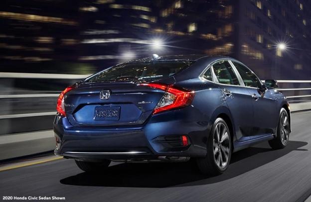 Blue 2020 Honda Civic Sedan drives up a highway at night in a city.