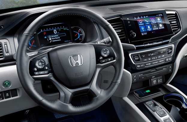 Interior front steering wheel, dashboard, infotainment and center console inside a 2020 Honda Pilot.
