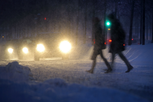 Two silhouettes cross a street in front of a line of headlights in a nighttime snow storm.
