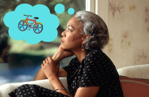 A woman sits and wonders about a bicycle.