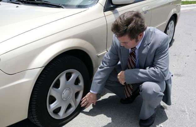 Man in a suit checks the pressure of a flat tire on his car