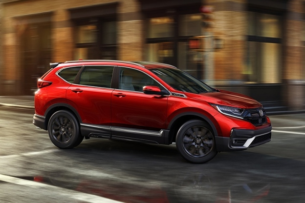 Red 2020 Honda CR-V drives through a city