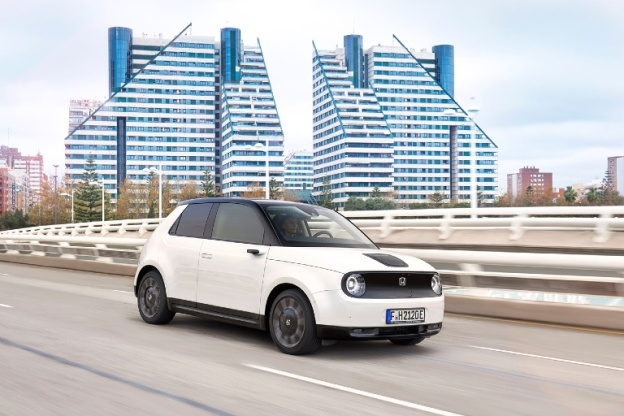 White Honda e drives on highway in front of futuristic buildings