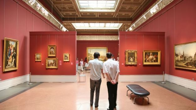 Two people standing in a museum